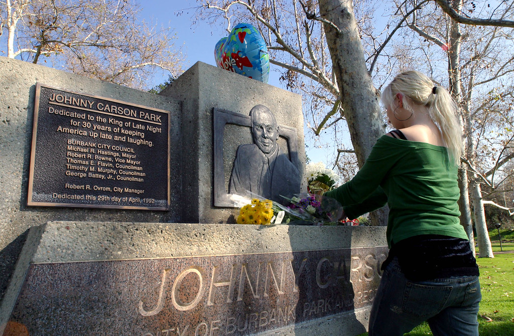 ". ** CORRECTS LATE SHOW TO TONIGHT SHOW STARRING JOHNNY CARSON ** Fan Lindsay Neumann, 23, from Burbank, Calif., brings flowers to the dedication sculpture at the Johnny Carson Park in Burbank, Calif., across from the NBC studios where ""The Tonight Show Starring Johnny Carson\"" was taped, Sunday, Jan. 23, 2005. (AP Photo/Stefano Paltera)"
