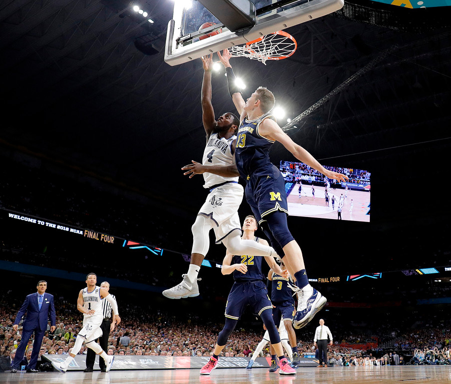 . Villanova\'s Eric Paschall (4) shoots against Michigan\'s Moritz Wagner (13) during the second half in the championship game of the Final Four NCAA college basketball tournament, Monday, April 2, 2018, in San Antonio. (AP Photo/David J. Phillip)