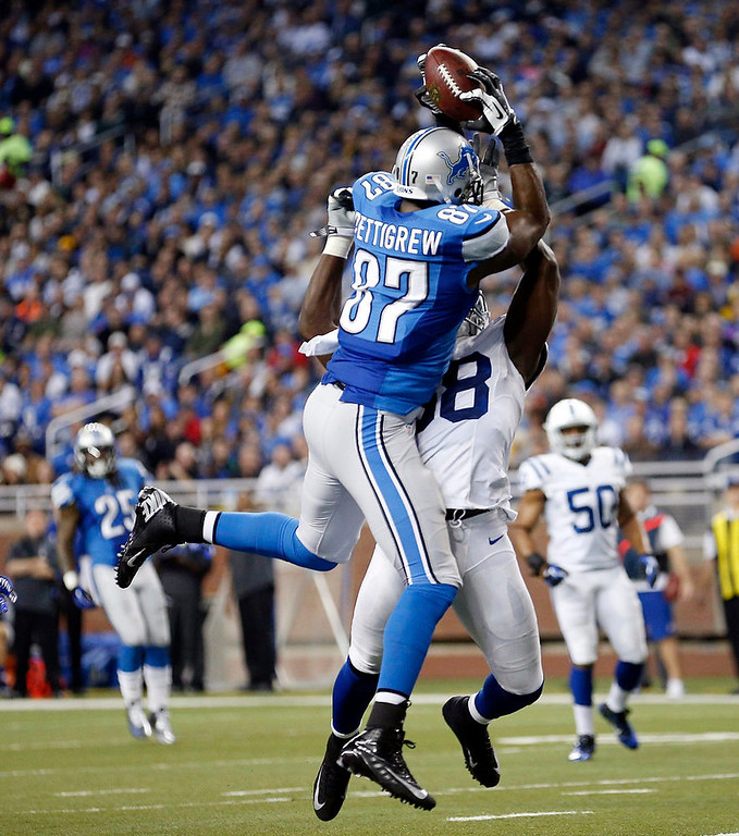 . Detroit Lions tight end Brandon Pettigrew (87), defended by Indianapolis Colts inside linebacker Moise Fokou (58), catches the ball before falling into the end zone after a 16-yard reception for a touchdown during the first quarter of an NFL football game at Ford Field in Detroit, Sunday, Dec. 2, 2012. (AP Photo/Rick Osentoski)