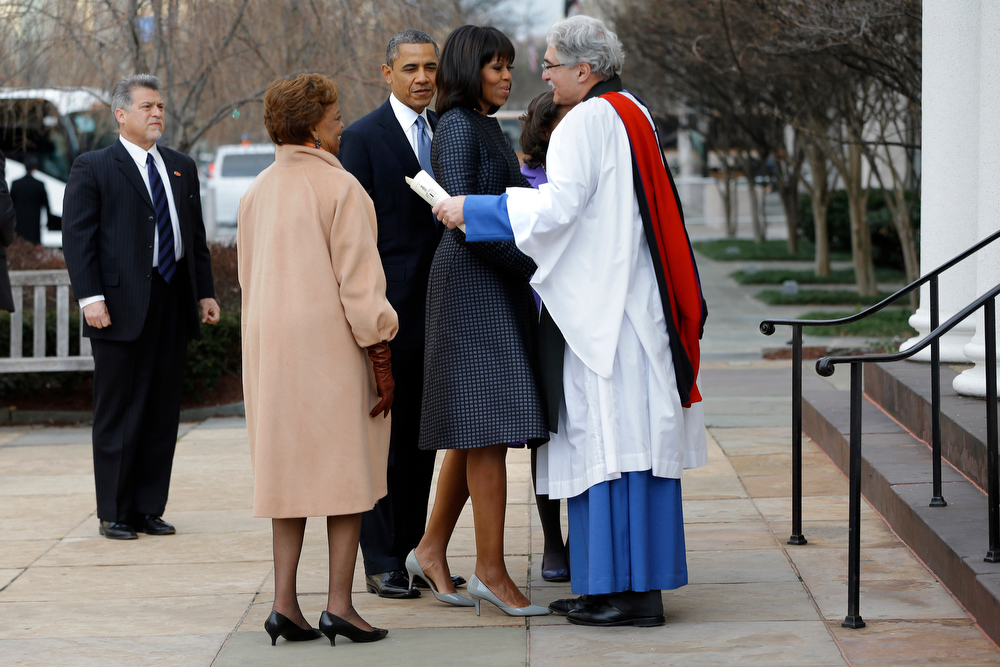 Description of . First lady Michelle Obama is greeted by Rev. Luis Leon at St. John's Church in Washington, Monday, Jan. 21, 2013, as the first family arrived for a church service during the 57th Presidential Inauguration. (AP Photo/Jacquelyn Martin)