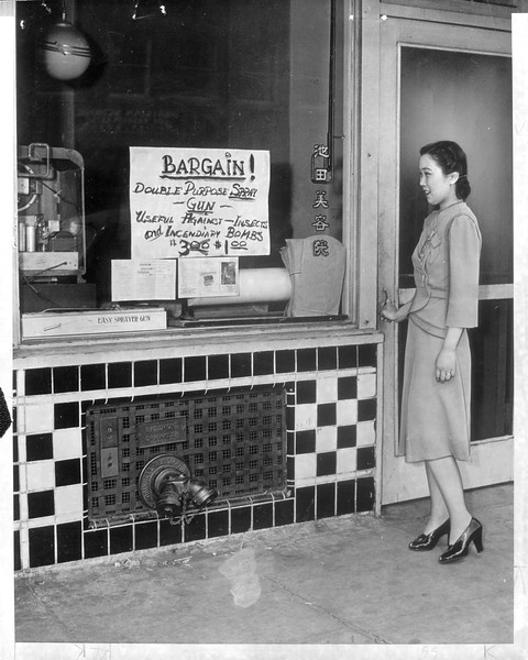 """""""Standing in the almost deserted 'Little Tokyo' Mrs. Jack Iwata surveys a typical sign for sale of an unneeded incendiary bomb spray gun in the rush to close out stock before evacuation.""""--caption on photograph"""