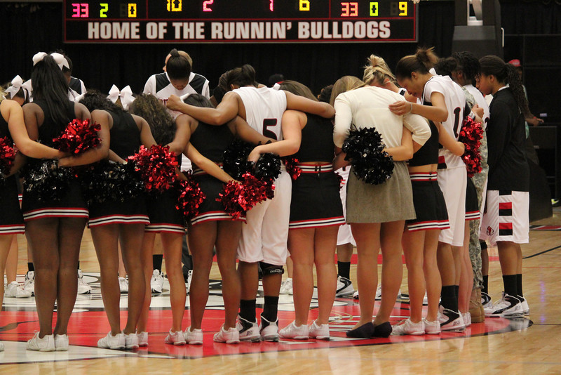 GWU Cheerleaders and Womens Basketball pray at together at the end of the game.