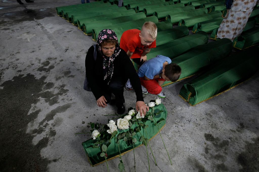 . A Bosnian  woman lays a flower on a coffin of a baby, among 409 newly identified Srebrenica victims,  at the Potocari memorial cemetery near Srebrenica, 160 kilometers east of Sarajevo, Bosnia and Herzegovina, Tuesday, July 9, 2013. A burial ceremony for 409 victims will be held on Thursday, July 11, 2013 in Potocari, on the 18th anniversary of the Srebrenica tragedy when in summer 1995 Bosnian Serb forces stormed the enclave and systematically killed thousands of Bosnian Muslims. (AP Photo/Amel Emric)