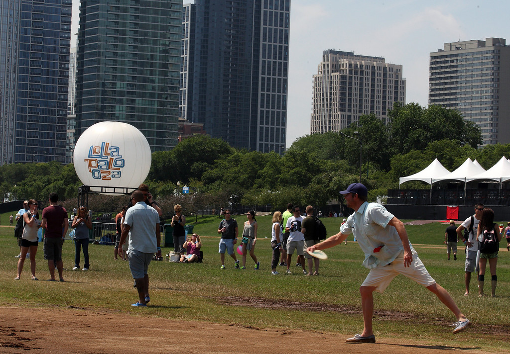 . A man throws a frisbee as fans begin entering day 1 of Lollapalooza 2013 at Grant Park on Friday, August 2, 2013 in Chicago. (Photo by Steve Mitchell/Invision/AP)