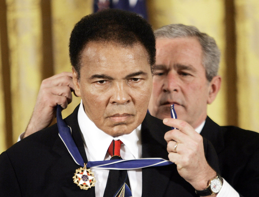 Description of . President Bush presents the Presidential Medal of Freedom, Wednesday, Nov. 9, 2005, to boxer Muhammad  Ali in the East Room of the White House.  (AP Photo/Evan Vucci)