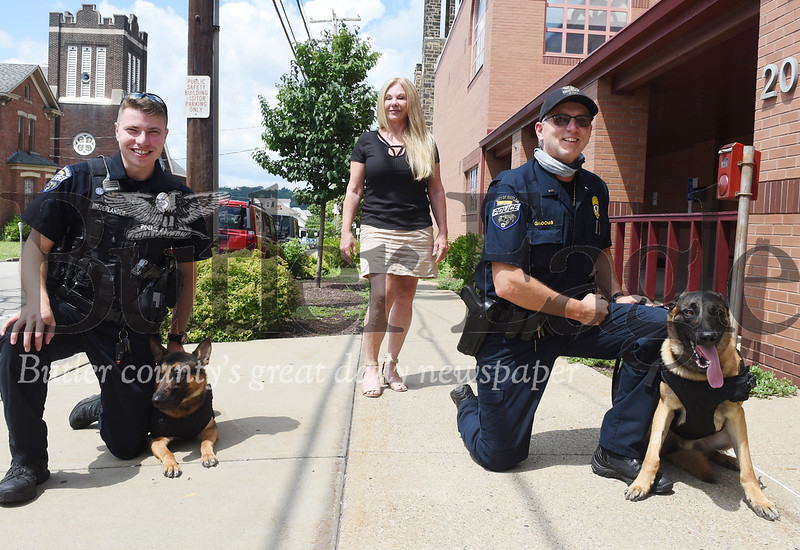 Harold Aughton/Butler Eagle: The Butler Police Department received new vests for their canine unit thanks to a donation from Corina Diehl. From left, Andrew Niederlander and his dog, Rico, Corina Diehl, and Brian Grooms and his dog, Chooch.