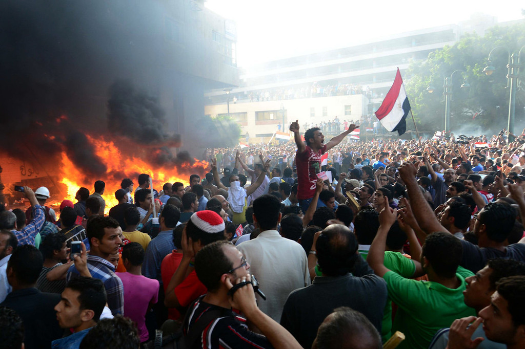. Opponents of Egypt\'s Islamist President Mohammed Morsi chant slogans as fire rages at the Muslim Brotherhood headquarters in Alexandria, Friday, June 28, 2013. Thousands of backers and opponents of Egypt\'s Islamist president held competing rallies in the capital Friday and new clashes erupted between the two sides in the country\'s second largest city, Alexandria, in a prelude to massive nationwide protests planned by the opposition this weekend demanding Mohammed Morsi\'s removal.  (AP Photo/Heba Khamis)
