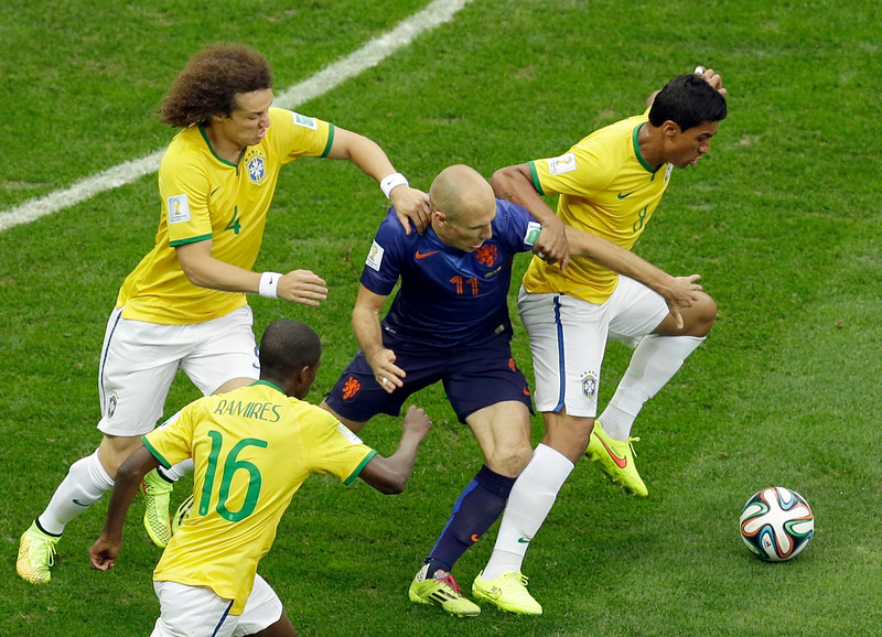 . Netherlands\' Arjen Robben fights for the ball with Brazil\'s Paulinho, right, and Brazil\'s David Luiz during the World Cup third-place soccer match between Brazil and the Netherlands at the Estadio Nacional in Brasilia, Brazil, Saturday, July 12, 2014. (AP Photo/Themba Hadebe)