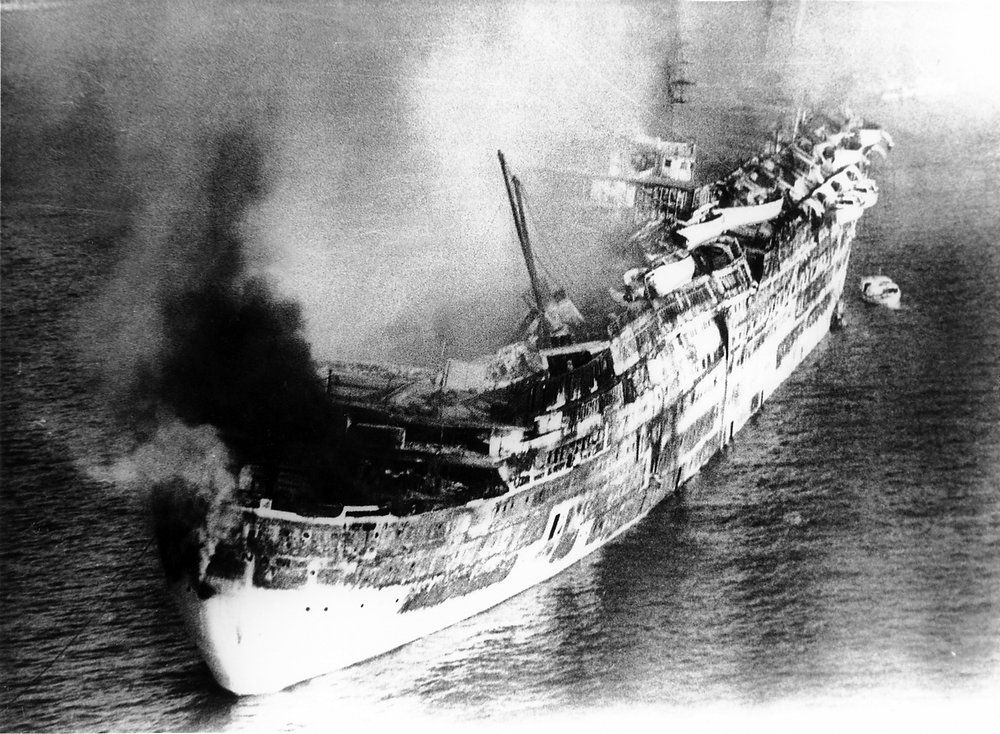 Description of . The former luxury liner Queen Elizabeth, her side buckling amidships, begins to collapse inwards upon her self in Hong Kong harbor on Jan. 10, 1972, after nearly 24 hours of raging fire. (AP Photo)