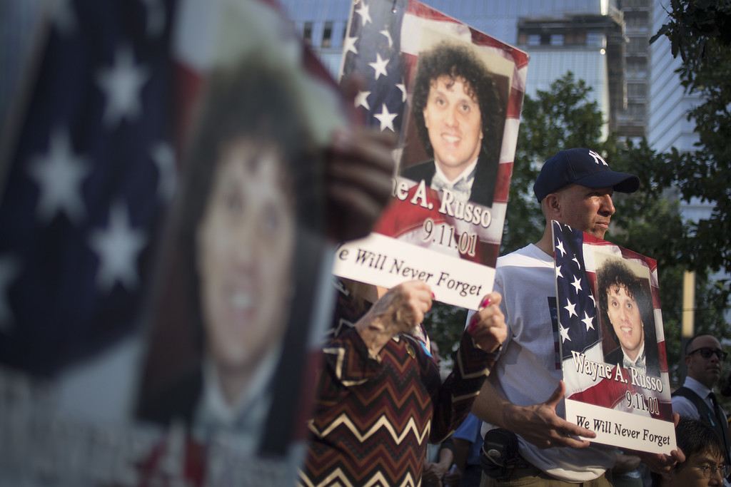 . Family and friends of Wayne A. Russo hold his images while attending the 9/11 Memorial ceremonies marking the 12th anniversary of the 9/11 attacks on the World Trade Center on September 11, 2013 in New York City.  (Photo by Adrees Latif-Pool/Getty Images)