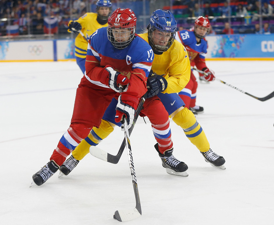 . Cecilia Ostberg of Sweden battles with Yekaterina Smolentseva of Russia for control of the puck during the 2014 Winter Olympics women\'s ice hockey game at Shayba Arena, Thursday, Feb. 13, 2014, in Sochi, Russia. (AP Photo/Petr David Josek)