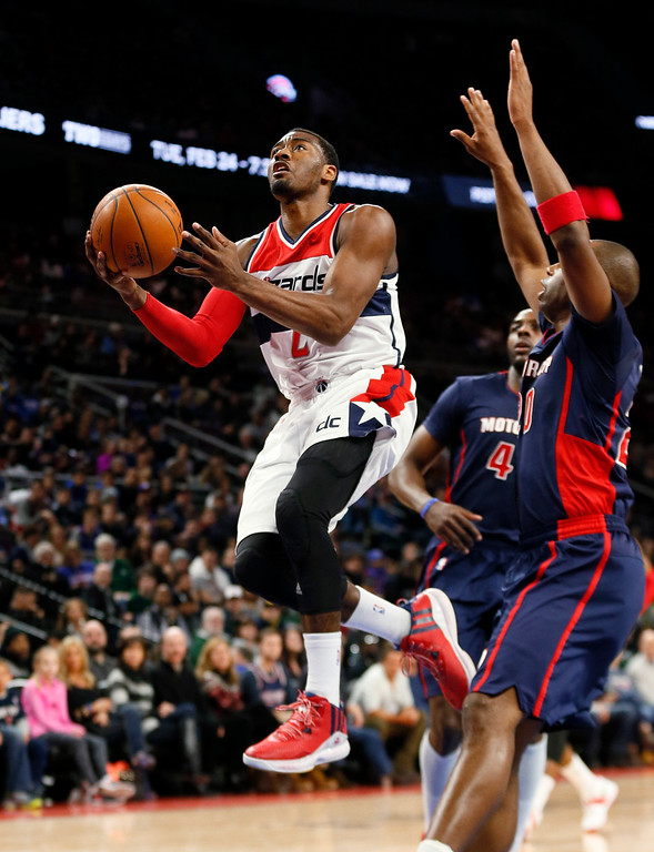 . Washington Wizards guard John Wall (2) drives on Detroit Pistons guard Jodie Meeks (20) in the second half of an NBA basketball game in Auburn Hills, Mich., Sunday, Feb. 22, 2015. (AP Photo/Paul Sancya)