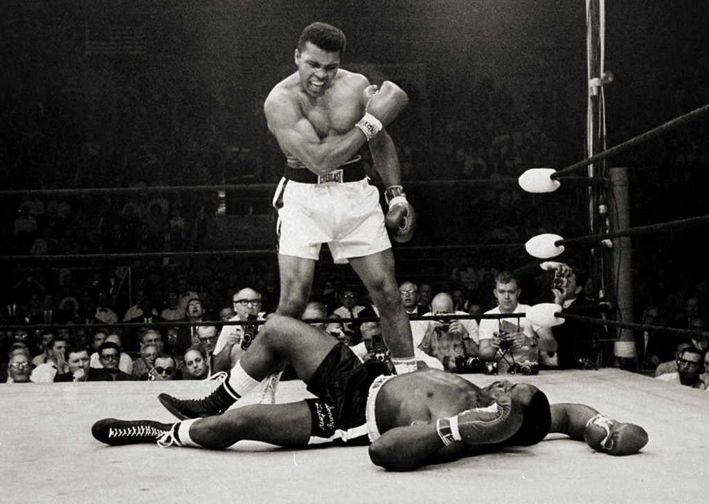 . Heavyweight champion Muhammad Ali stands over fallen challenger Sonny Liston, shouting and gesturing shortly after dropping Liston with a short hard right to the jaw on May 25, 1965, in Lewiston, Maine.  The bout lasted only one minute into the first round.  Ali is the only man ever to win the world heavyweight boxing championship three times.  He also won a gold medal in the light-heavyweight division at the 1960 Summer Olympic Games in Rome as a member of the U.S. Olympic boxing team.  In 1964 he dropped the name Cassius Clay and adopted the Muslim name Muhammad Ali.  (AP Photo/John Rooney)