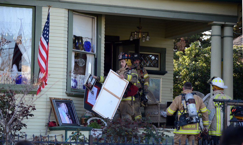 . Firefighters remove valuables from a home on fire in the 400 block of H Street  in Antioch, Calif., on Wednesday, March 13, 2013. (Susan Tripp Pollard/Staff)
