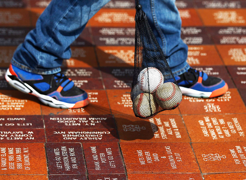 . A New York Mets fan walks with a bag of baseballs outside CitiField before the New York Mets opening day MLB National League baseball game against the San Diego Padres in New York, April 1, 2013.  REUTERS/Shannon Stapleton