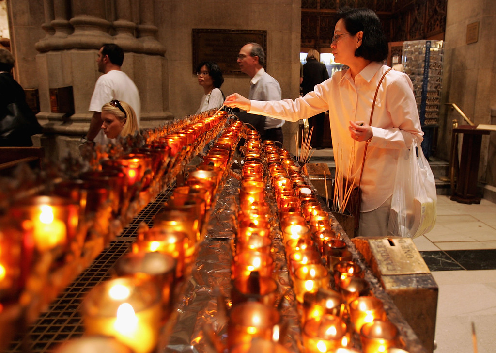 . A woman lights a candle at St. Patrick\'s Cathedral after the election of a new Pope is announced  April 19, 2005 in New York City. The newly elected Pope is Benedict XVI, known as German Cardinal Joseph Ratzinger.  (Photo by Spencer Platt/Getty Images)