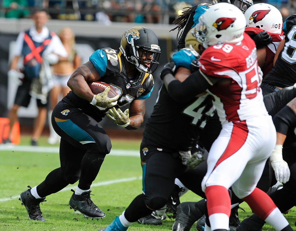 . Jacksonville Jaguars running back Maurice Jones-Drew (32) charges past the Arizona Cardinals defense, including linebacker Marcus Ben,ard (59) for a 1-yard touchdown during the first half of an NFL football game in Jacksonville, Fla., Sunday, Nov. 17, 2013. (AP Photo/Stephen Morton)