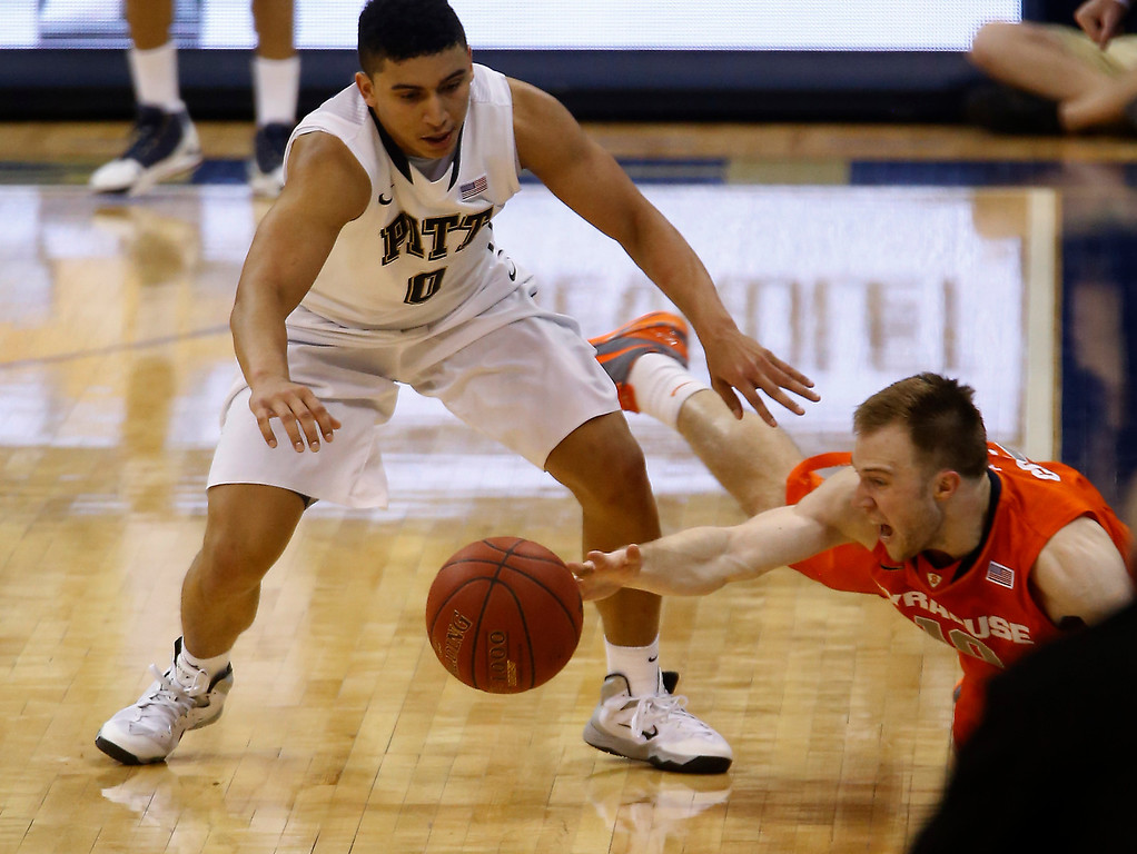 . Pittsburgh\'s James Robinson, left, and Syracuse\'s Trevor Cooney go for a loose ball during the second half of an NCAA college basketball game Wednesday, Feb. 12, 2014, in Pittsburgh. (AP Photo/Keith Srakocic)