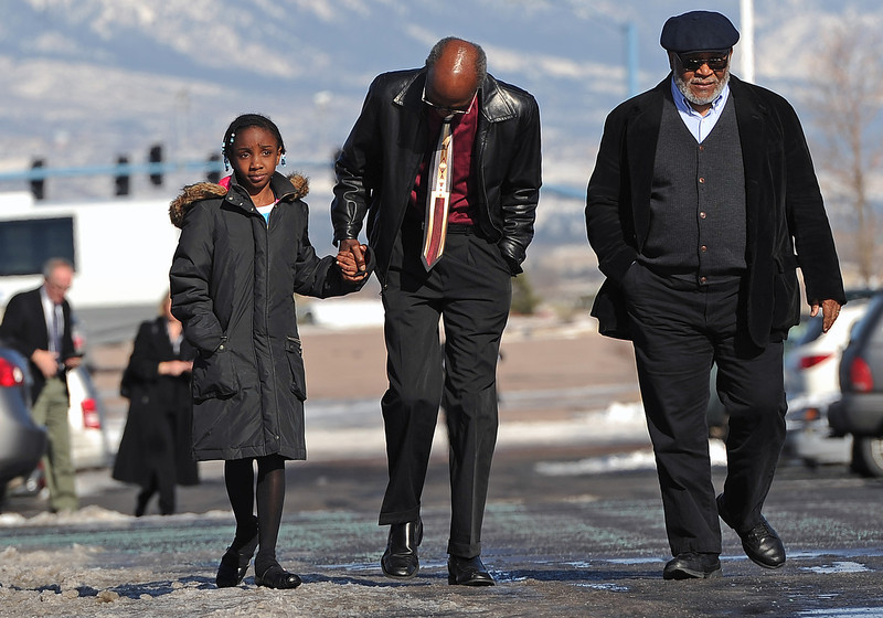 . Webster Hendricks, middle, holds the hand of his daughter Iy\'jaenae, 9, as they walk with John Riley, all of Denver,  towards the church for the public memorial.  Hendricks was a friend of Tom Clements.  Friends, family and  corrections and police officers from all over the nation came to the public memorial service for Tom Clements  at New Life Church in Colorado Springs on March 25, 2013.  Hundreds turned out to pay their respects to Clements who was the executive director of the Colorado Department of Corrections, Tom Clements, was shot and killed as he opened the door to his Monument home on March 19, 2013.  (Photo By Helen H. Richardson/ The Denver Post)