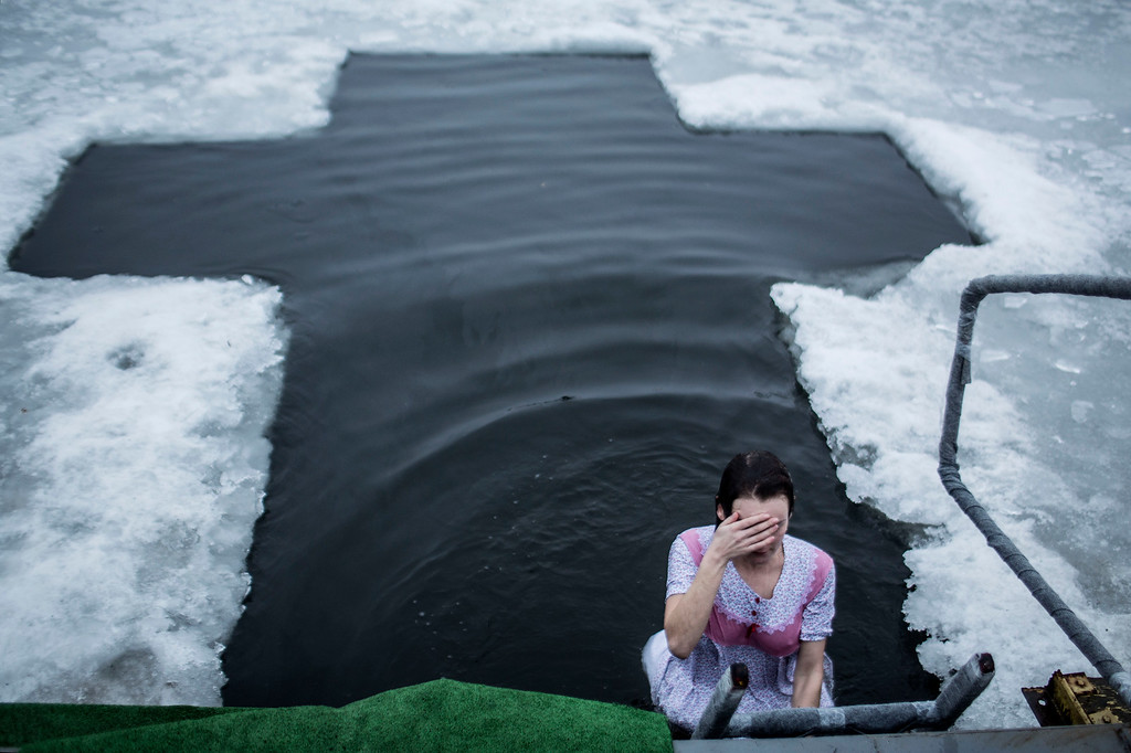 . A Ukrainian woman takes a bath in the waters of lake of Sherbakova Park during the celebration of the Orthodox Epiphany in Donetsk, Ukraine. Monday, Jan. 19, 2015.  Orthodox Christians  celebrate Epiphany on Jan. 19 , following old Julian calendar. (AP Photo/Manu Brabo)