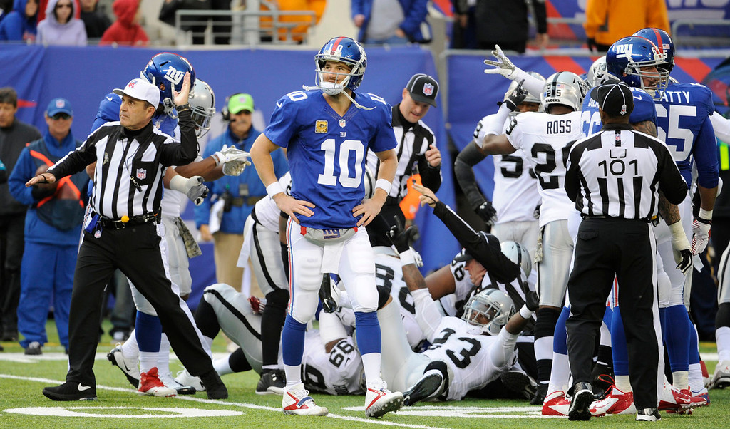 . New York Giants quarterback Eli Manning (10) walks away as an official, left, signals for the ball in favor of the Oakland Raiders after a Giants turnover during the first half of an NFL football game on Sunday, Nov. 10, 2013, in East Rutherford, N.J. (AP Photo/Bill Kostroun)