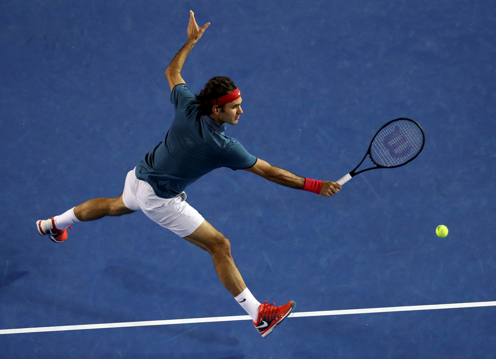 . Roger Federer of Switzerland leaps for a shot to Rafael Nadal of Spain during their semifinal at the Australian Open tennis championship in Melbourne, Australia, Friday, Jan. 24, 2014.(AP Photo/Eugene Hoshiko)