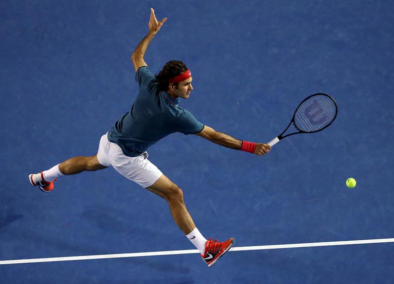 . Roger Federer of Switzerland leaps for a shot to Rafael Nadal of Spain during their semifinal at the Australian Open tennis championship in Melbourne, Australia, Friday, Jan. 24, 2014.(AP Photo/Eugene Hoshiko)