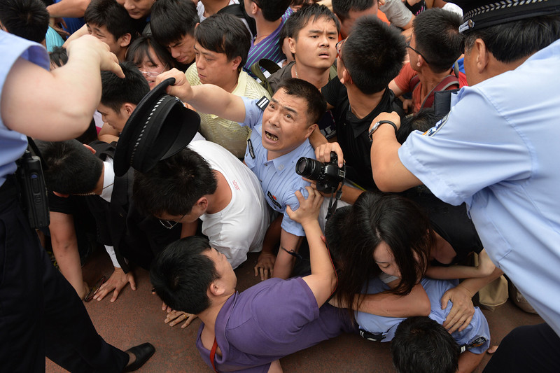 """. People fall in a stampede to see football superstar David Beckham at Tonji University in Shanghai on June 20, 2013. Beckham\'s visit to China turned \""""chaotic\"""" on June 20 after at least five people were hurt in a stampede as fans rushed to see him, local media and an AFP photographer at the scene said.  PETER PARKS/AFP/Getty Images"""