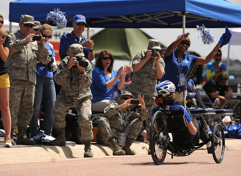 . Army personnel cheer on their athlete Ramina Oraha during the women\'s Handcycle and Recumbent cycle race. The fourth annual Warrior Games cycling event took started and finished at Falcon Stadium on the grounds of the Air Force Academy in Colorado Springs, CO on May 12, 2013.  HRH Prince Harry was on hand to start the race as well as to hand out medals at the finish line.   A total of 260 wounded, ill and injured service members and veterans came to compete in the week long games.  Members of the Army, Marine Corps, Navy/Coast Guard/Air Force. Special Operations and the British Armed Forces all took part in the competition.  Other events included in the Warrior Games are shooting, sitting volleyball, track & field and wheelchair basketball.  (Photo by Helen H. Richardson/The Denver Post)