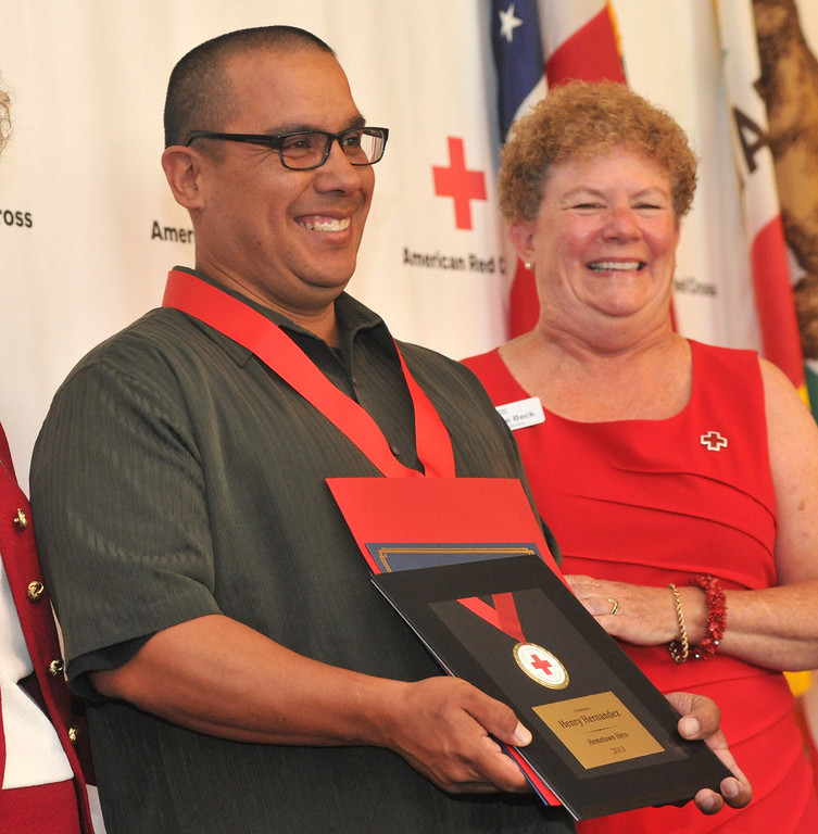 . Bus driver Henry Hernandez receives a medal as  the Rio Hondo Chapter of the American Red Cross honors 14 people for their part in performing extraordinary acts during their Hometown Heroes luncheon at the Quiet Cannon in Montebello on Thursday June 27, 2013. (SGVN/Staff Photo by Keith Durflinger)
