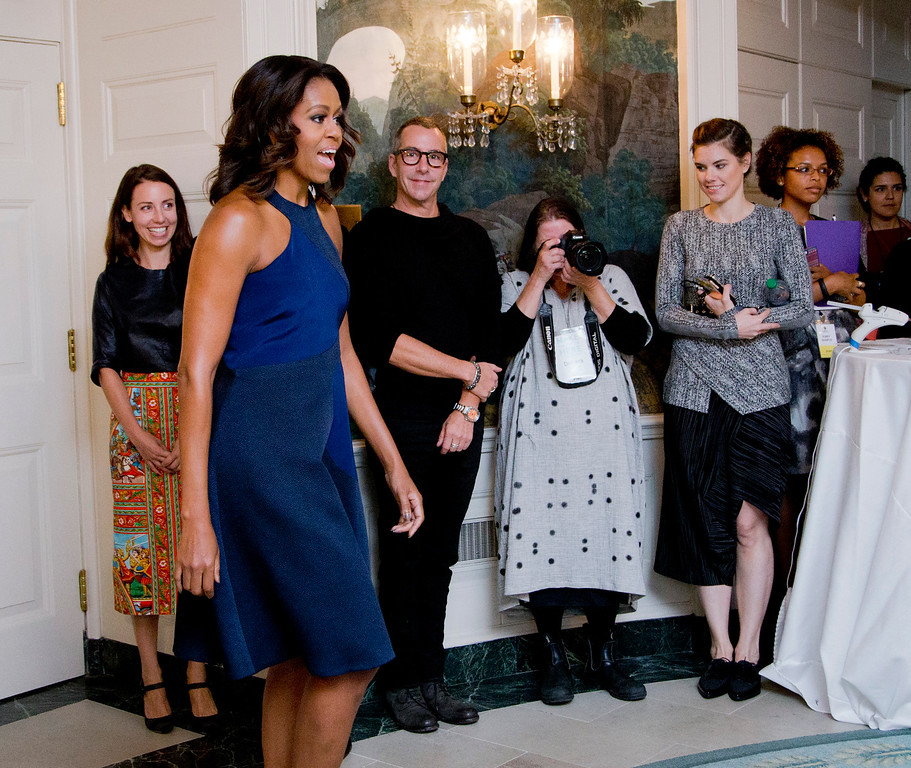 . First lady Michelle Obama greets participants of the Fashion Education Workshop in the Diplomatic Room of the White House in Washington, Wednesday, Oct. 8, 2014. The first lady is wearing a navy sleeveless dress with a full skirt and a racer style front designed by Natalya Koval, student from Fashion Institute of Technology, who won a design competition.   (AP Photo/Manuel Balce Ceneta)