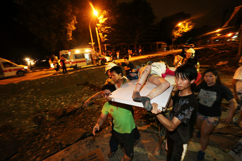 . Residents carry a wounded person following a blast in the city of Kaohsiung in southern Taiwan early on August 1, 2014. The explosion, that is believed to have been caused by a gas leak, killed at least four people and wounded 186 others.   AFP PHOTO / STRINGER  /AFP/Getty Images