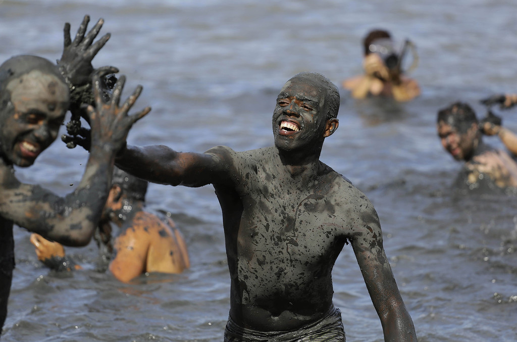 ". Mud-covered revelers frolic in ocean waters during the ""Bloco da Lama\"" or \""mud street partyî in Paraty, Brazil, Saturday, March 1, 2014. \""Bloco da Lama\"" was founded in 1986 by two local teens who became local Carnival sensations after they appeared in the cityís historic downtown covered in mud following a crab hunting expedition in a nearby mangrove forest, said Diana Rodrigues, who was hired by Paraty\'s City Hall to explain the history of the \""Bloco\"" to foreigners. (AP Photo/Nelson Antoine)"