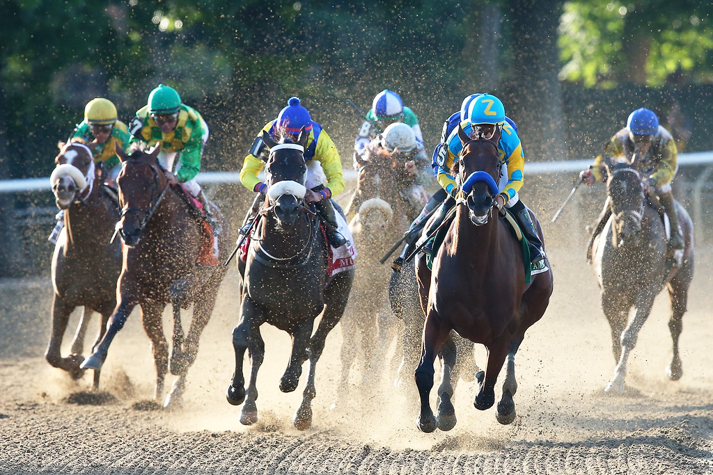 . American Pharoah #5, ridden by Victor Espinoza, leads the field out of the fourth turn during the 147th running of the Belmont Stakes at Belmont Park on June 6, 2015 in Elmont, New York.  (Photo by Elsa/Getty Images)
