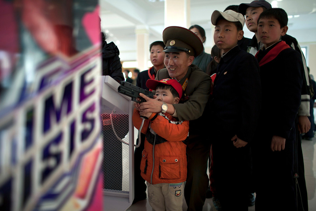 ". A North Korean military officer plays a game called ""Time Crisis\"" with his son at an amusement park in Pyongyang, North Korea, Tuesday, April 16, 2013. (AP Photo/Alexander F. Yuan)"