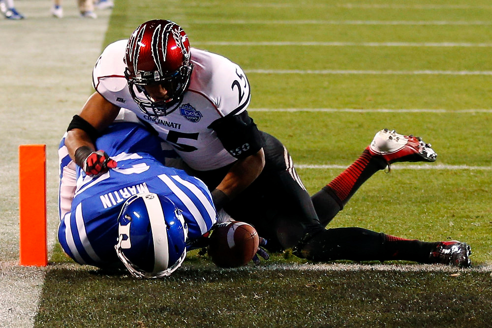 Description of . Duke's Ross Martin (35) fumbles the ball short of the end zone as Cincinnati's Arryn Chenault (25) defends during the first half of the Belk Bowl NCAA college football game in Charlotte, N.C., Thursday, Dec. 27, 2012. (AP Photo/Chuck Burton)