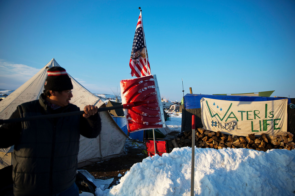. Benji Buffalo, a Grovan Native American from Montana, shovels snow outside his tent at the Oceti Sakowin camp where people have gathered to protest the Dakota Access oil pipeline in Cannon Ball, N.D., Saturday, Dec. 3, 2016. (AP Photo/David Goldman)