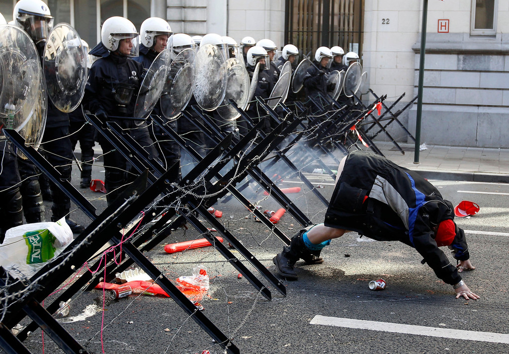 . A demonstrator shows his bottom to riot police during a protest by European workers and trade union representatives to demand better job protection in the European Union countries in Brussels March 24, 2011. REUTERS/Thierry Roge