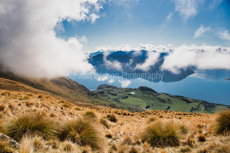 Looking down through the passing clouds to Lake Wanaka on the way up Roys Peak Track