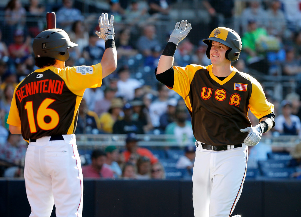 . U.S. Team\'s Chance Sisco, of the Baltimore Orioles, right, high-fives teammate Andrew Benintendi (16) home run during the fourth inning of the All-Star Futures baseball game against the World Team, Sunday, July 10, 2016, in San Diego. (AP Photo/Lenny Ignelzi)