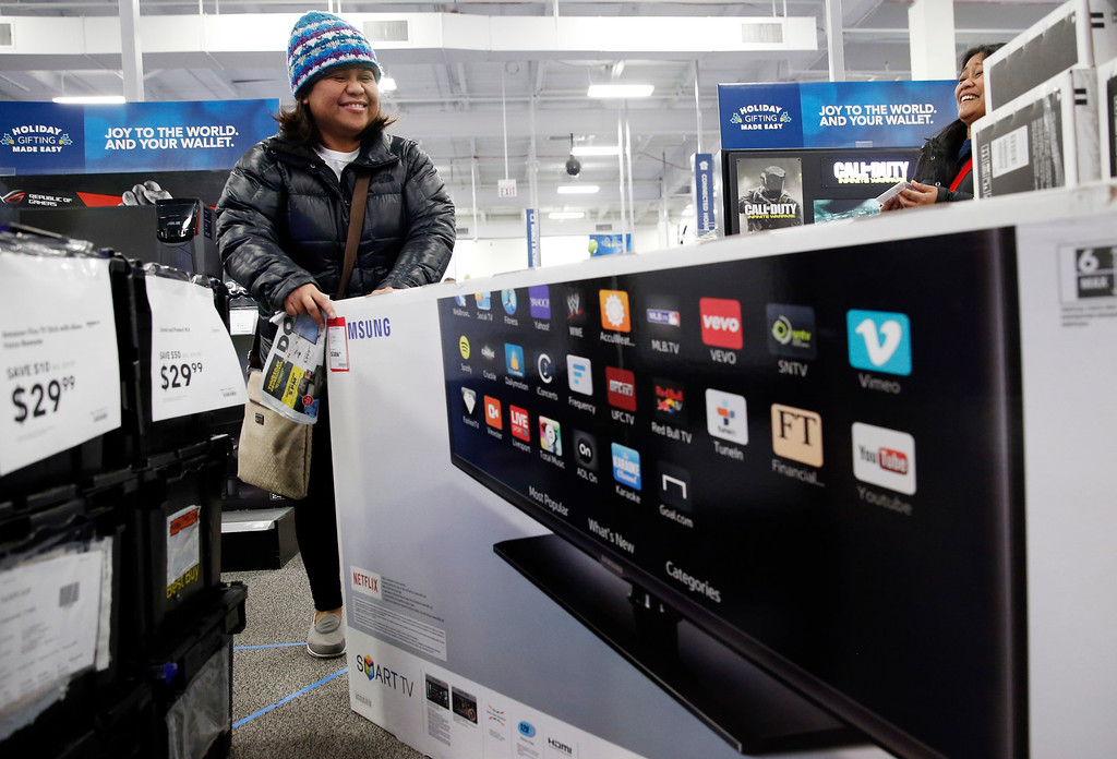 . A shopper carries a smart television at a Best Buy store on Friday, Nov. 25, 2016, in Skokie, Ill.  Shoppers were on the hunt for deals and were at the stores for entertainment Friday as malls opened for what is still one of the busiest days of the year, even as the start of the holiday season edges ever earlier.  (AP Photo/Nam Y. Huh)