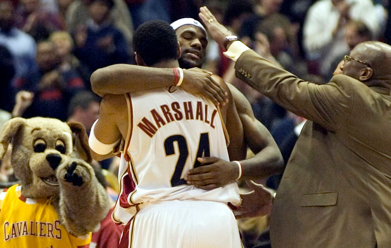 . PHOTO BY DAVID RICHARD LeBron James is congratulated by teammate Donyell Marshall and head coach Mike Brown after James\' bucket in overtime gave the Cavaliers a 120-118 win over visiting Charlotte.