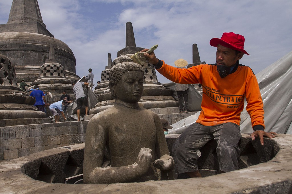 . A Volunteer (R) cleans volcanic ash from a Buddha figure at the ancient Borobudur temple in Magelang, Central Java province on February 17, 2014 following the eruption of the Mount Kelud volcano. Borobudur, a Buddhist temple and Indonesia\'s national treasure built between the eighth and ninth century is located about 200 kilometers west of Kelud volcano, was blanketed by ash and temporarily closed to the public.  AFP PHOTO / SURYO WIBOWO/AFP/Getty Images