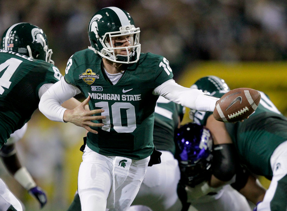 Description of . Michigan State quarterback Andrew Maxwell (10) hands off against TCU during the first half of the Buffalo Wild Wings Bowl NCAA college football game, Saturday, Dec. 29, 2012, in Tempe, Ariz. (AP Photo/Matt York)