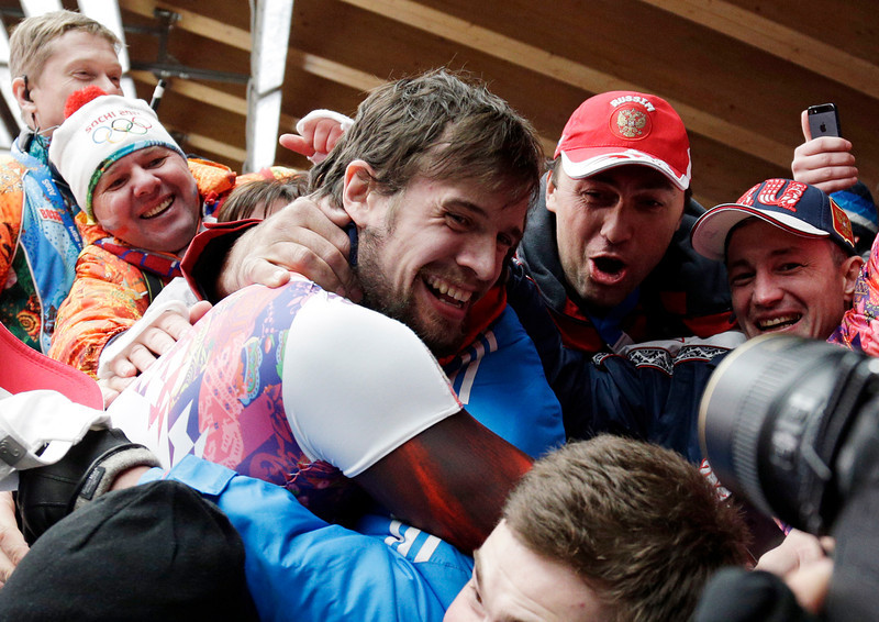 . Alexander Tretiakov of Russia celebrates with fans and supporters in the finish area after he won the gold medal during the men\'s skeleton competition at the 2014 Winter Olympics, Saturday, Feb. 15, 2014, in Krasnaya Polyana, Russia.  (AP Photo/Michael Sohn)