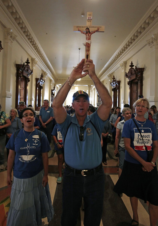 . Michael Benavides of Austin holds up a crucifix and leads a group of pro-life supporters into the Texas State capitol on July 1, 2013 in Austin, Texas. This is the first day of a second legislative special session called by Texas Gov. Rick Perry to pass a restrictive abortion law through the Texas legislature. The first attempt was defeated after opponents of the law were able to stall the vote until after first special session had ended.  (Photo by Erich Schlegel/Getty Images)