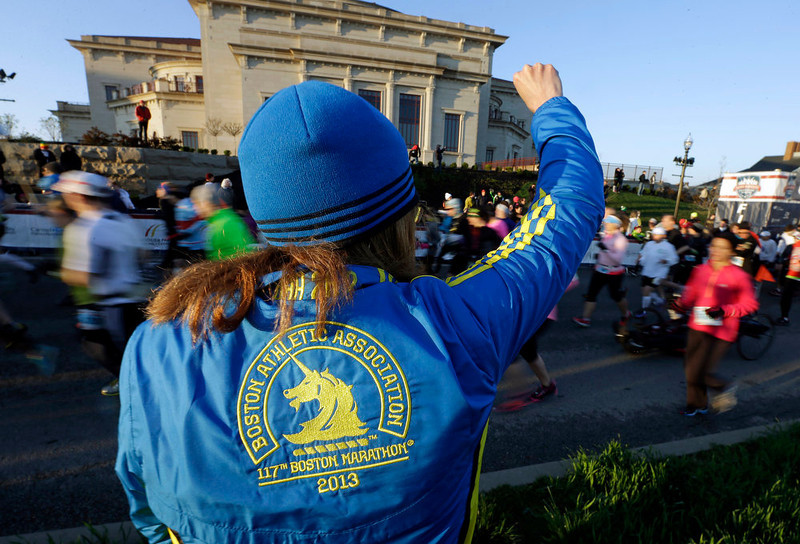 . 2013 Boston Marathon runner Brenda Campbell of Chesterton, Ind., cheers for runners as they start the Carmel Marathon Saturday, April 20, 2013, in Carmel, Ind. Before the start organizers held a moment of silence for those injured and killed in the Boston Marathon bombings. Runners also wore blue and yellow ribbons.  (AP Photo/Darron Cummings)