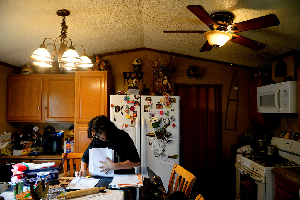. MILLIKEN, CO - DECEMBER 18: Martha Gutierrez, manager of the Evergreen Mobile Home Park, sorts through documents pertaining to flood remodeling. Residents of the mobile home park say that the city of Milliken has not done enough to assist in the rebuilding of the 33-unit residential sub division that was struck hard by recent floods that ravaged much of northern Colorado. (Photo by AAron Ontiveroz/The Denver Post)