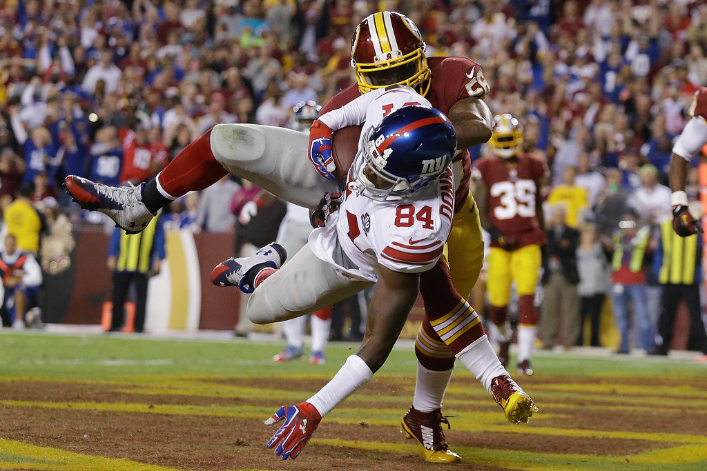 . New York Giants tight end Larry Donnell (84) heads to the turf in the end zone after pulling in a touchdown pass under pressure from Washington Redskins inside linebacker Perry Riley (56) during the first half of an NFL football game in Landover, Md., Thursday, Sept. 25, 2014. (AP Photo/Patrick Semansky)