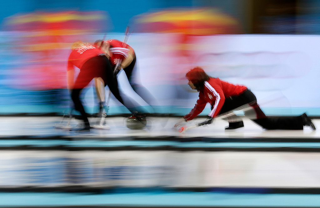 . Switerland\'s skip Mirjam Ott, right, delivers the rock to her teammates during the women\'s curling competition against Sweden at the 2014 Winter Olympics, Thursday, Feb. 13, 2014, in Sochi, Russia. (AP Photo/Wong Maye-E)